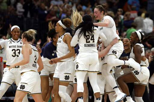 Notre Dame players celebrate their 81-76 triumph against top rival UConn to advance to national title game.