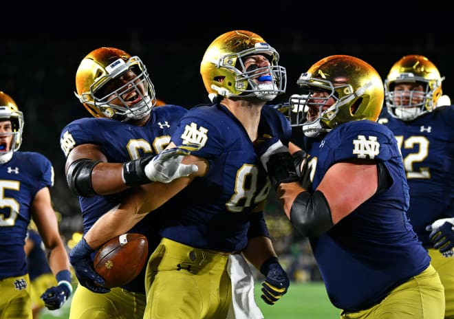 Notre Dame tight end Cole Kmet celebrating his touchdown against USC with offensive linemen (Andris Visockis)