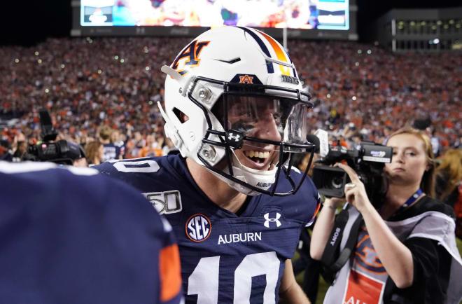 Bo Nix (10) celebrates on the field following Auburn's Iron Bowl win over Alabama.