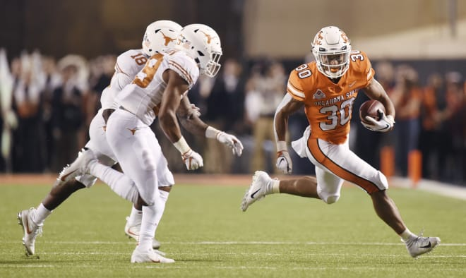 Chuba Hubbard runs past a pair of Texas defenders last October.