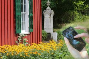 phone image overlaid on image of flower bed at Genesee Country Village & Museum