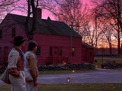 two young men walk through Genesee Country Village at night