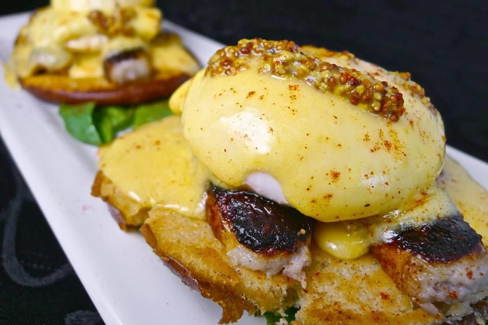 The Speakez Benedict, two poached eggs, and sausage with dijon mustard and hollandaise sauce over two toasted buns