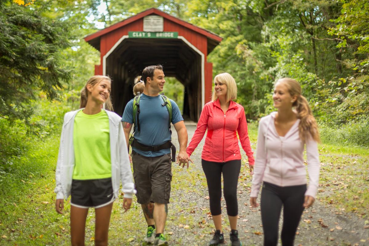Family walking with a covered bridge in Little Buffalo State Park PA