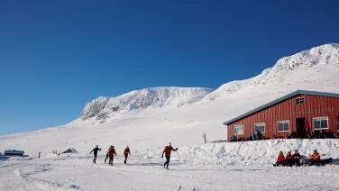 Prestholtseter in winter, red cabin, many people on crosscountry