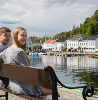 Couple relaxing next to the Risør harbour Norway
