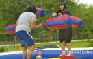 two adults jousting