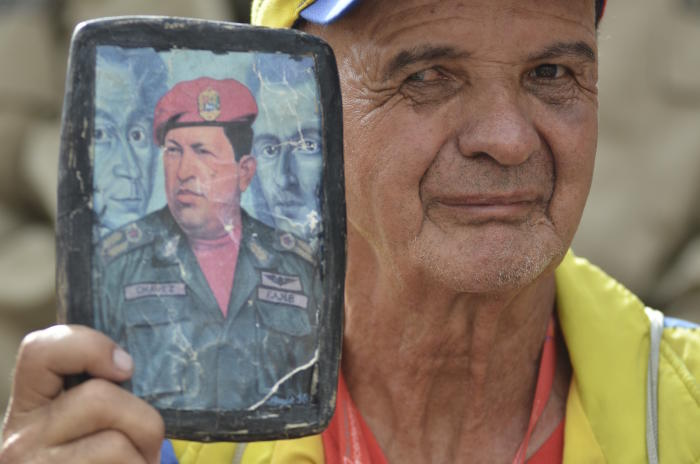 A man holding a portrait of former Venezuelan President Hugo Chavez poses for a photo during a pro-government rally in Caracas, Venezuela on October 1, 2016. Picture: Carlos Becerra/Anadolu Agency/Getty Images