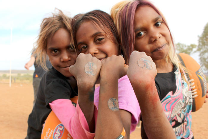 <em>Children from Ntaria in the Northern Territory show off temporary tattoos of &lsquo;Milpa&rsquo; the trachoma goanna who is part of the education effort developed by Indigenous Eye Health at the University of Melbourne. Picture: Rachael Ferguson, IEH</em>