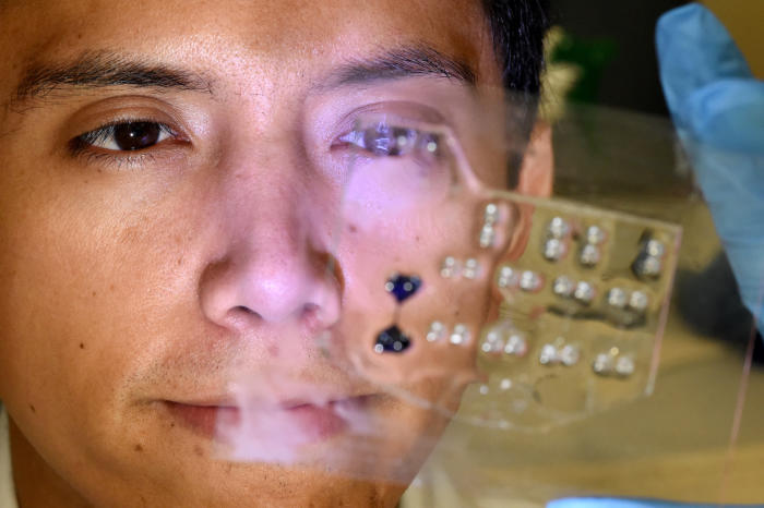 "Fernando Rafael Jativa Guzman, PhD candidate within the University of Melbourne's School of Engineering, holds a version of the ""on-a-chip"" obstacle course for lung spheroids showing chambers and connecting corridor highlighted with blue dye. Picture: Paul Burston, University of Melbourne."
