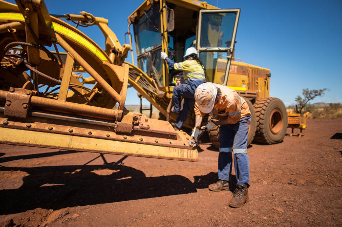 Indigenous workers carry out running repairs on giant machinery as part of their daily work at Christmas Creek mine in the Pilbara, Western Australia. Picture supplied
