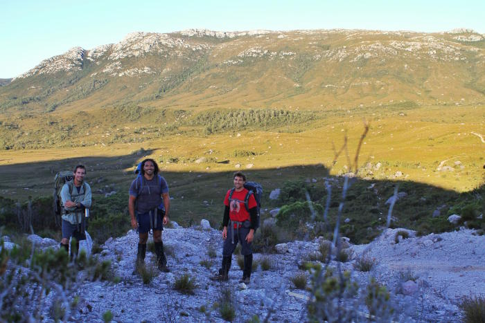 """Hiking through the Tyndall Ranges in Tasmania's west. We conduct exploratory field campaigns into remote locations to ascertain the potential of sites. Often these hikes take multiple days, and up to a week, depending on remoteness."" - Dr Fletcher (middle, with Scott Nichols and Steven Willison). Picture: Michael-Shawn Fletcher (on a self-timer)"