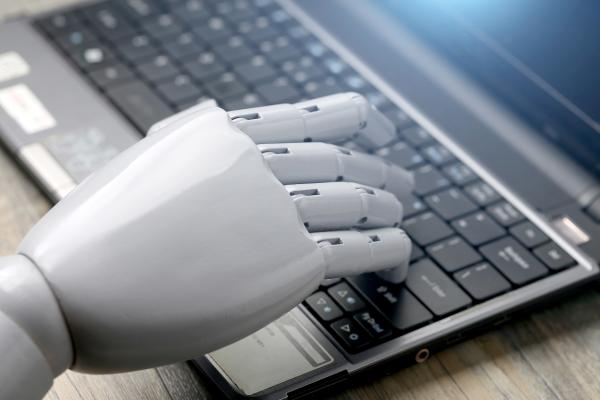 A robot hand typing on a keyboard