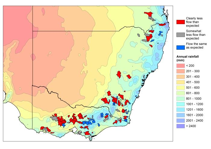 Map of the catchments studied showing in red those with less flow than expected, superimposed on annual rainfall.